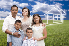Young Hispanic Family Standing in Grass Field with Ghosted House Royalty Free Stock Photography