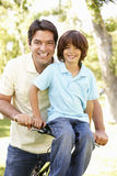 Young Hispanic Father And Son Cycling In Park Royalty Free Stock Image