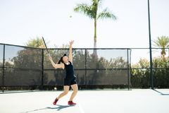 Serving on the tennis court. Young hispanic female tennis player standing on base line tossing the ball and about to server the ball Royalty Free Stock Image
