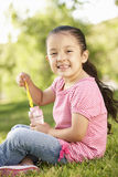 Young Hispanic Girl Blowing Bubbles In Park Stock Photo
