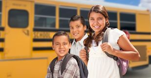 Young Hispanic Girl and Boys Walking Near School Bus stock photography