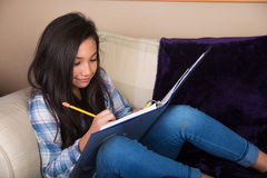 Young hispanic girl doing homework on the couch Royalty Free Stock Photography