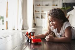 Young Hispanic girl lying on the floor in the sitting room playing with a toy digger truck stock photos