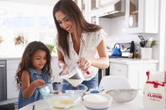 Young Hispanic girl making cake in the kitchen with help from her mum, waist up stock image
