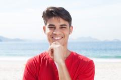 Young hispanic guy at beach looking at camera Royalty Free Stock Photography