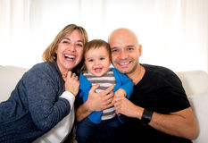 Young hispanic happy mother and father holding little son couch Stock Images