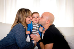 Young hispanic happy mother and father kissing little son couch Royalty Free Stock Images