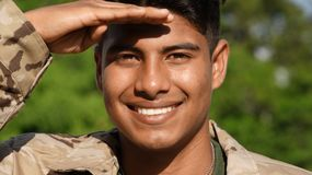 Male Soldier Saluting. A young hispanic male teen Stock Image