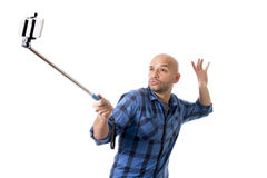Young Hispanic man in casual shirt having fun shooting mobile phone selfie picture holding stick Stock Photos