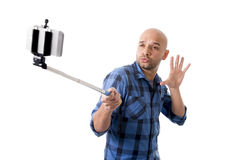 Young Hispanic man in casual shirt having fun shooting mobile phone selfie picture holding stick. Young Hispanic man in casual shirt having fun shooting mobile Royalty Free Stock Images
