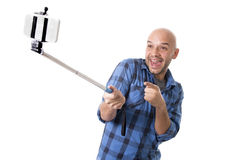Young Hispanic man in casual shirt having fun shooting mobile phone selfie picture holding stick. Young Hispanic man in casual shirt having fun shooting mobile Stock Photo