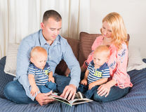 Young Hispanic Man With Caucasian Woman Reading to Twin Baby Boy. Young Hispanic Man With Blue Shirt and Young Caucasian Woman Wearing Pink Blouse Reading to Stock Photo