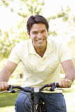 Young Hispanic Man Cycling In Park Stock Images