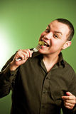 Young hispanic man eating. With green background Stock Image