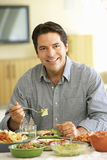 Young Hispanic Man Enjoying Meal At Home Royalty Free Stock Images