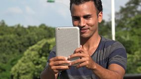 Young Hispanic Man Filming Using Tablet. A handsome adult hispanic man stock footage