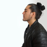 Young hispanic man with gathered hair done bow in black dress and black leather jacket Stock Image
