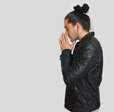 Young hispanic man with gathered hair done bow wearing black t-shirt and black leather jacket, with his hands clasped. In prayer position with crouched head stock photo