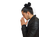 Young hispanic man with gathered hair done bow wearing black t-shirt and black leather jacket, with his hands clasped. In prayer position with crouched head royalty free stock images