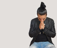 Young hispanic man with gathered hair done bow wearing black t-shirt and black leather jacket, with his hands clasped. In prayer position with crouched head royalty free stock photos