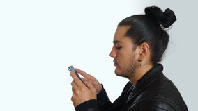 Young hispanic man with gathered hair done bow wearing black t-shirt and black leather jacket, sending a text message Stock Image
