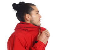 Young hispanic man with gathered hair done bow wearing black t-shirt and red jacket, hands stretching his jacket. Posing profile looking to the right Stock Photo