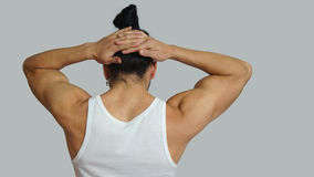 Young hispanic man with gathered hair done bow in white sleeveless t-shirt, seen from back Royalty Free Stock Images