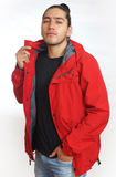Young hispanic man with gathered hair done in bun wearing black t-shirt and red jacket, with one hand on his pants pocket. Looking towards the camera Royalty Free Stock Image