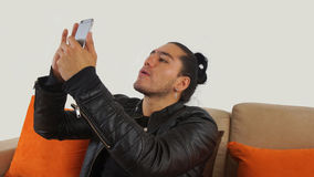 Young hispanic man with hair pulled up bun in black dress and black leather jacket sitting on a sofa. Looking at his mobile phone Stock Photo