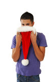 Young hispanic man hiding behind a Santa Hat Royalty Free Stock Photos