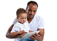 Young Hispanic man and little boy reading fairy tale on touch pad computer Royalty Free Stock Images