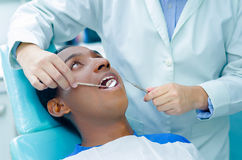 Young hispanic man lying in chair receiving dental treatment with mouth open, dentist hands wearing gloves holding tools. Working on patients teeth Royalty Free Stock Photo