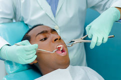Young hispanic man lying in chair receiving dental treatment with mouth open, dentist hands wearing gloves holding tools Royalty Free Stock Image