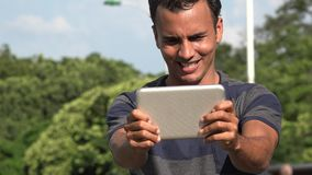 Young Hispanic Man Playing Games On Tablet. A handsome adult hispanic man stock video
