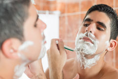 Young hispanic man shaving Stock Images