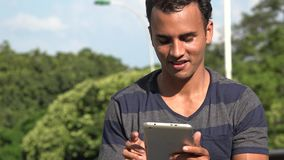 Young hispanic man texting using tablet. A handsome adult hispanic man stock video footage