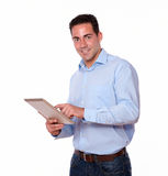 Young hispanic man using his tablet pc Stock Images