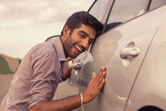 Young hispanic man wearing in formal shirt holding is petting his car royalty free stock image