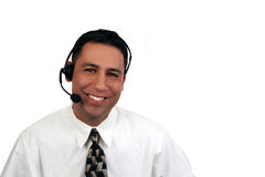 A young, hispanic office worker. Smiling and wearing a headset Royalty Free Stock Photos