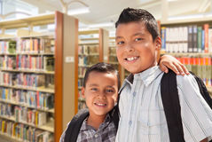 Young Hispanic Student Brothers In Library. Happy Young Hispanic Student Brothers In Library Stock Photos
