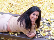 Young hispanic teen girl on bench. Young latina girl on stomach on bench with autumn leaves Stock Images