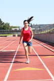 Young hispanic teen girl running on track. Young latina teen girl running on track shorts red top royalty free stock photography