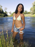 Young hispanic teen girl in swimsuit at river. Young latina teen girl at river in swim suit and shorts stock image