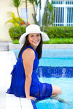 Young hispanic woman in blue dress relaxing by the swimming pool Stock Images