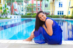 Young hispanic woman in blue dress relaxing by the swimming pool surrounded by flowers Royalty Free Stock Image