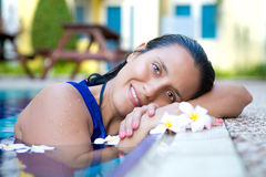 Young hispanic woman in blue dress relaxing by the swimming pool surrounded by flowers stock photos
