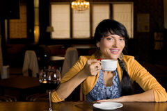Young Hispanic woman drinking coffee. Young Hispanic woman with her long hair in a plait drinking coffee sitting at a counter in a bar relaxing and smiling at royalty free stock photography