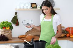 Young Hispanic woman in a green apron cooking in the kitchen. Housewife found a new recipe for her soup. What is it in. My pan stock images
