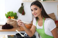 Young Hispanic woman in a green apron cooking in the kitchen. Housewife holding wooden spoon while smiling. Young Hispanic woman in a green apron cooking in the Royalty Free Stock Photography