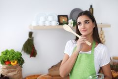 Young Hispanic woman in a green apron cooking in the kitchen. Housewife holding wooden spoon while smiling. Young Hispanic woman in a green apron cooking in the Stock Photo